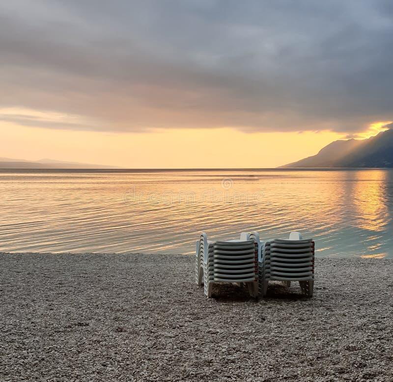 Gefaltete Strandstühle auf einem Pebble Beach gegen den Hintergrund von einem ruhigen sauberen Meer, von Bergen und von Sonnenunt lizenzfreie stockfotos