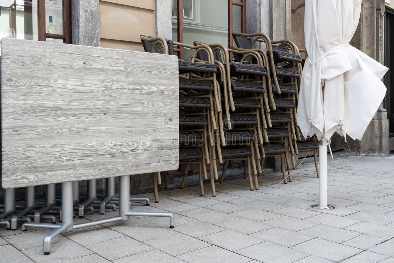 Gefaltete Tabellen und Stühle eines Straßencaféstands auf dem Bürgersteig lizenzfreies stockbild