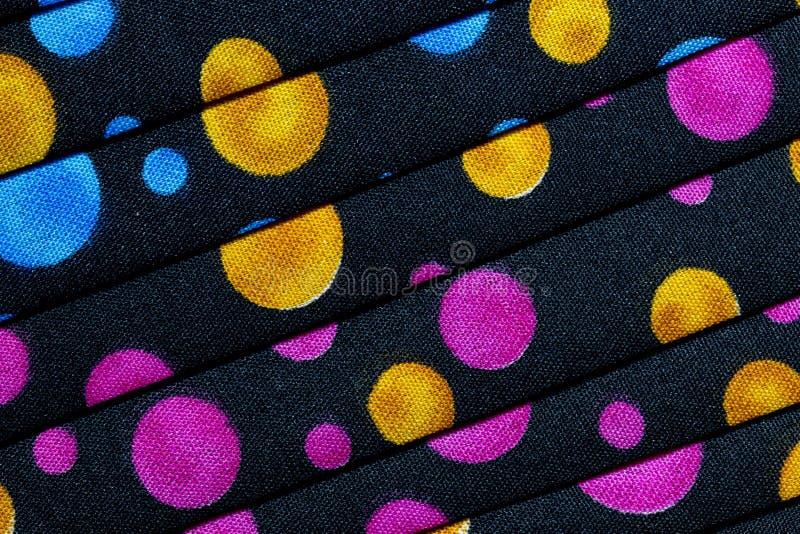 Gefaltetes Gewebe mit Rotem, Blauem, rosa, Gold und grüne Punkte/Kreise lizenzfreie stockbilder