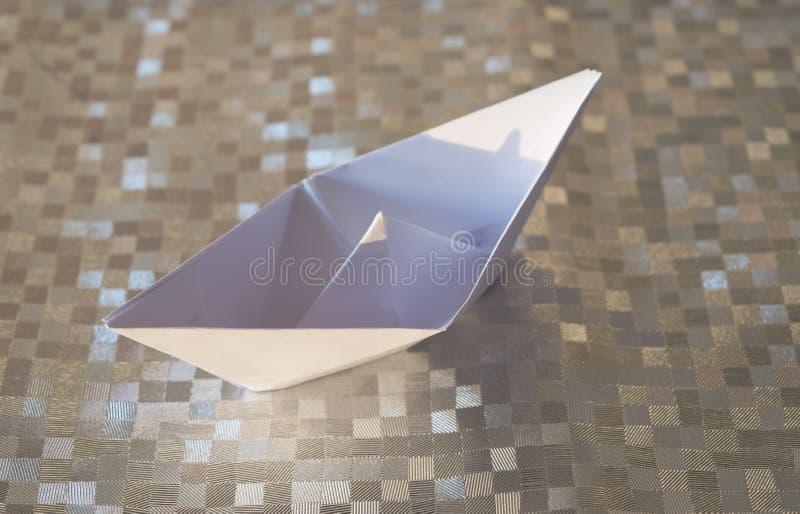 Gefaltetes Weißbuchschiff auf einem silbernen Hintergrund stockbilder