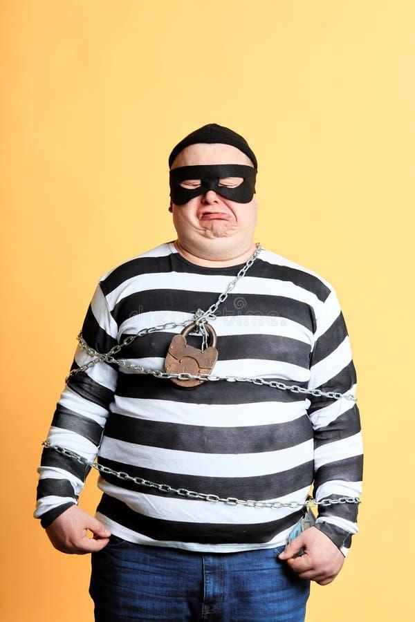 Gefangener in der Maske mit Kette um seine Körperstellung über gelbem Hintergrund lizenzfreie stockfotos