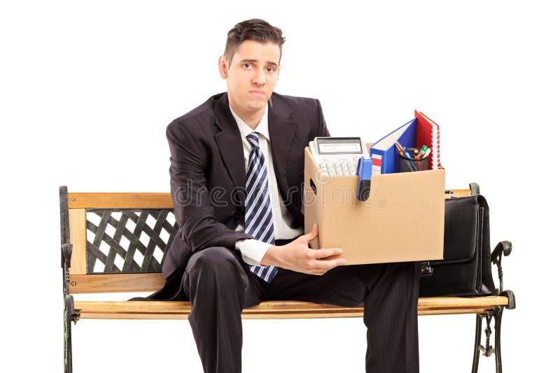 Gefeuerter Geschäftsmann, der einen Kasten mit seinem Material hält lizenzfreies stockfoto