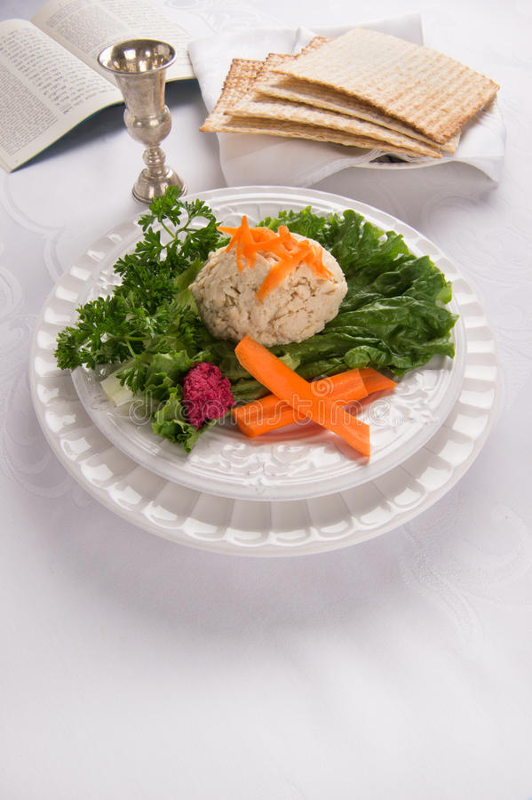 Gefilte Fish with Kidduch Cup, Matzah and Haggadah. Traditional Jewish passover food gefilte fish with carrots, parsley, horseradish, and lettuce on white linen royalty free stock images