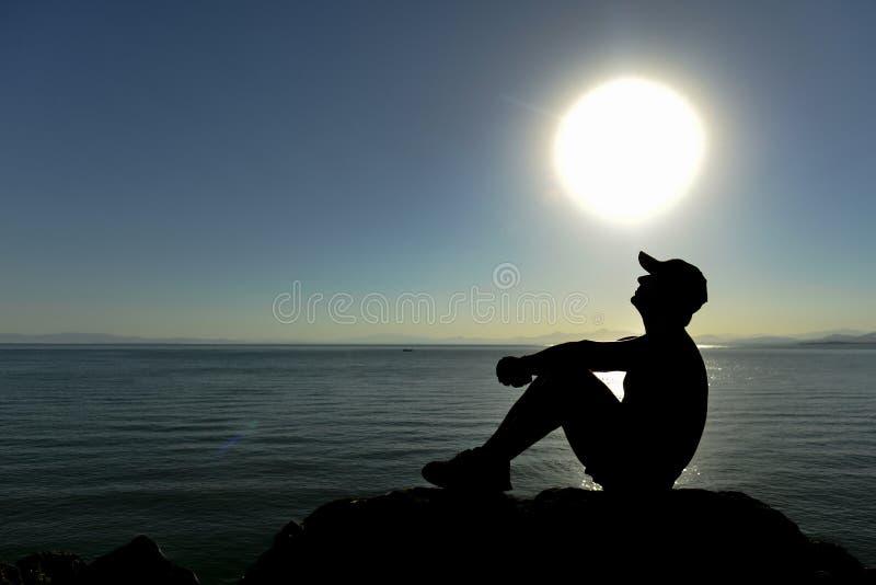 Gefiltreerde kleuren op en zonsopgang bij het strand, mens die denken letten op royalty-vrije stock foto