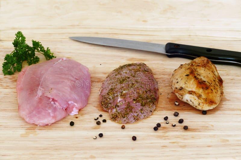Geflügelfleisch, roh, mariniert und auf hölzernem Brett gebraten stockbild