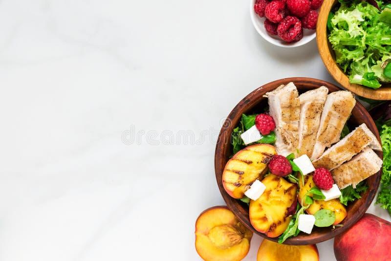 Geflügelsalat mit gegrilltem Pfirsich, Mischsalat, Feta und Himbeeren in einer Schüssel Gesunde Nahrung Beschneidungspfad eingesc lizenzfreie stockfotos