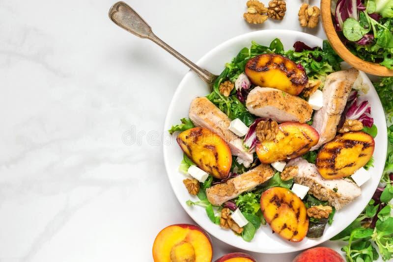 Geflügelsalat mit gegrilltem Pfirsich, Mischsalat, Feta und Walnüsse in einer Platte mit Gabel Gesunde Nahrung oberseite stockfoto