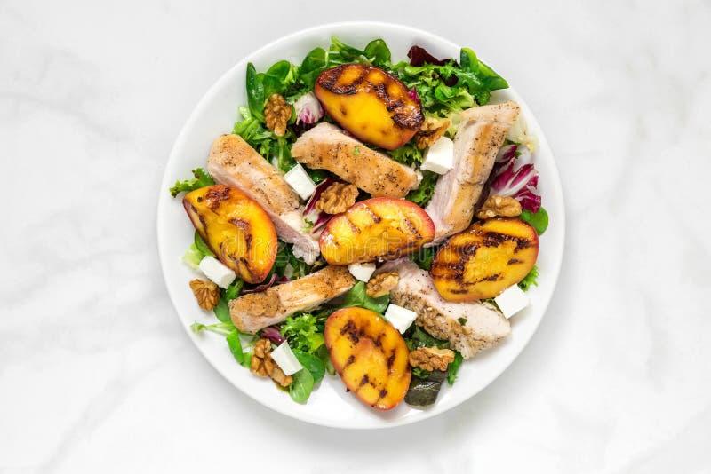 Geflügelsalat mit gegrilltem Pfirsich, Mischsalat, Feta und Walnüsse in einer Platte Gesunde Nahrung lizenzfreie stockfotos