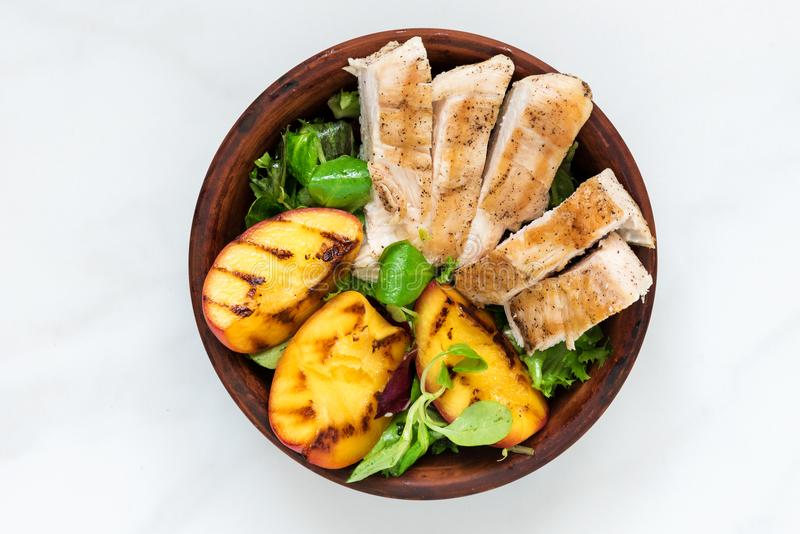 Geflügelsalat mit gegrilltem Pfirsich und Mischsalat in einer Schüssel Gesunde Nahrung stockfotografie