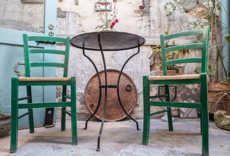 Geflochtene Stühle mit Metalltabelle stockfotos