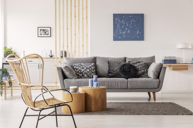 Geflochtener Stuhl nahe bei Holzklotzcouchtisch im modernen Wohnzimmerinnenraum stockbilder