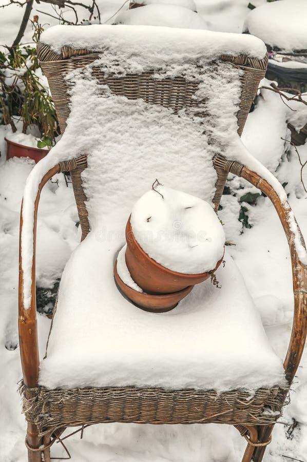 Geflochtener Stuhl umfasst mit Schnee stockbild