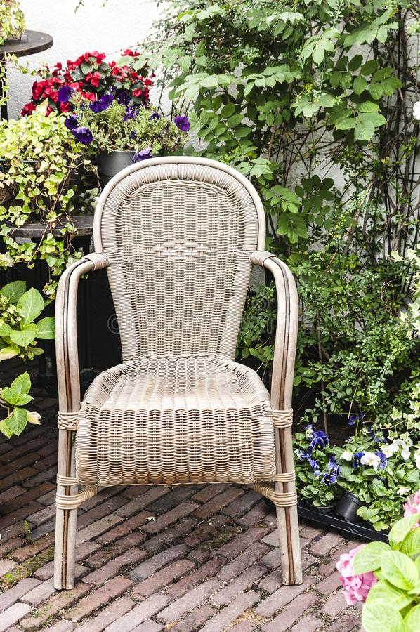 Geflochtener Stuhl umgeben durch Anlagen lizenzfreie stockfotos