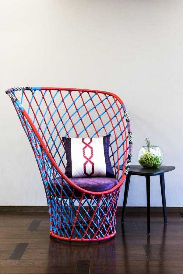 Geflochtener Stuhl vor einer einfachen Wand lizenzfreies stockbild