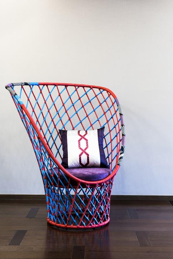 Geflochtener Stuhl vor einer einfachen Wand lizenzfreie stockfotos