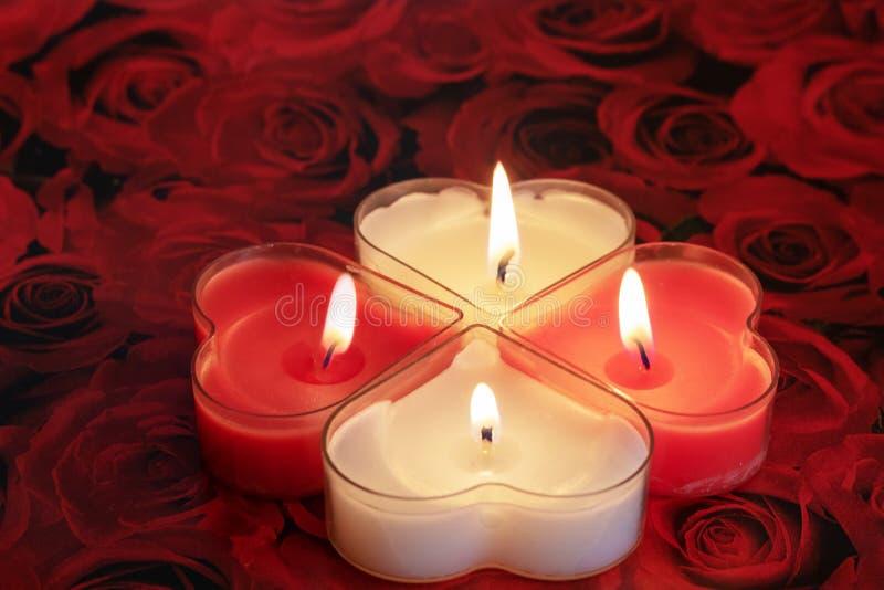 Geformte Kerze des Herzens brennend rot und weiß lizenzfreies stockfoto