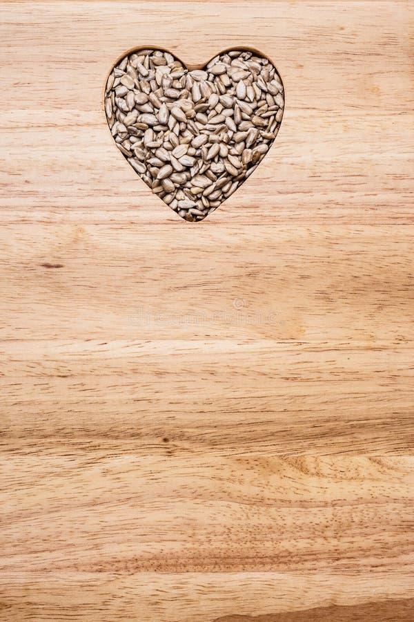 Geformte Sonnenblumensamen des Herzens auf Holzoberfl?che lizenzfreies stockbild