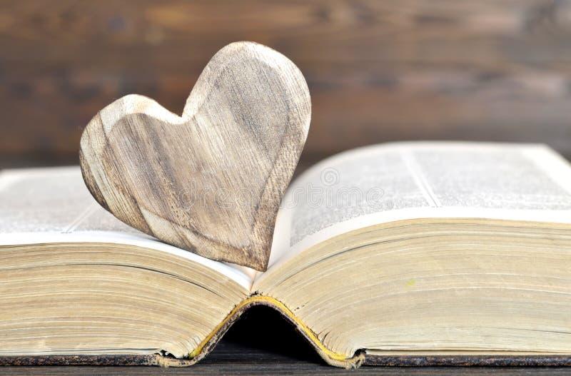 Geformte Verzierung des Herzens und ein altes Buch lizenzfreie stockbilder
