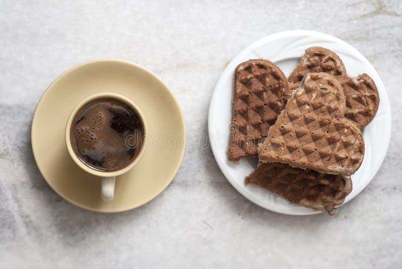 Geformte Waffeln und Kaffee des Herzens auf Tabelle lizenzfreies stockbild