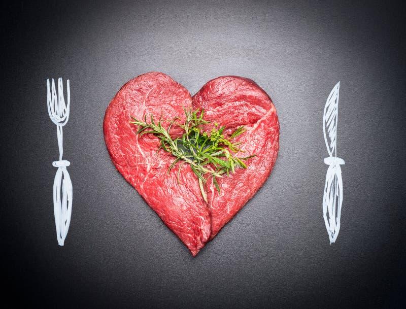 Geformter roher Hieb des Herzens des Fleisches Fleischliebe mit gemaltem Tischbesteck: Gabel und Messer Dunkler Tafelhintergrund lizenzfreie stockbilder