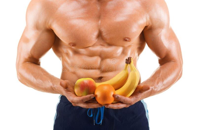 Geformter und gesunder Körpermann, der die frischen Früchte, geformtes Abdominal- halten, lokalisiert auf Weiß ist lizenzfreie stockfotos
