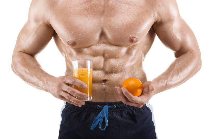 Geformter und gesunder Körpermann, der ein Glas mit dem Saft und Orange, geformtes Abdominal-, lokalisiert auf Weiß hält stockbild