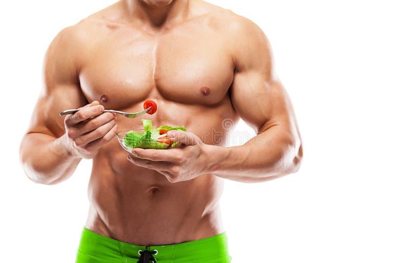 Geformter und gesunder Körpermann, der eine frische Salatschüssel, geformte AB hält stockbilder