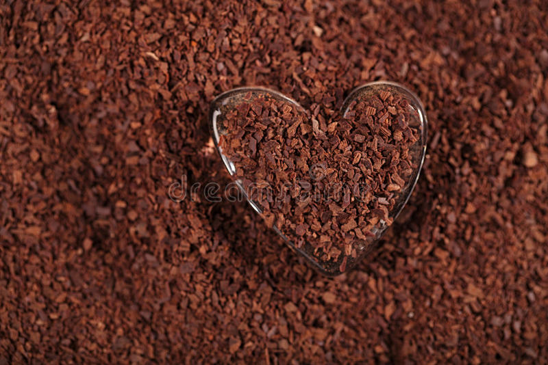 Geformtes Glas des Herzens mit zerriebener dunkler Schokolade stockfotos