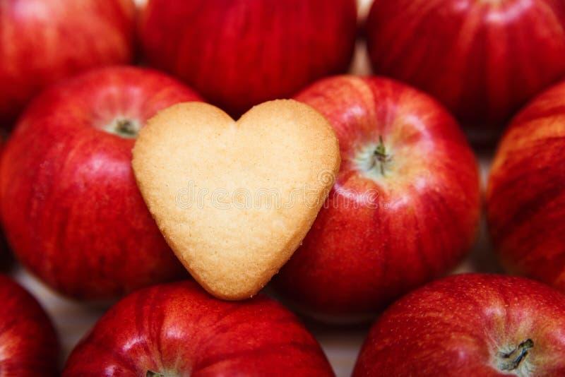 Geformtes Plätzchen des Herzens auf den roten Äpfeln stockfotografie