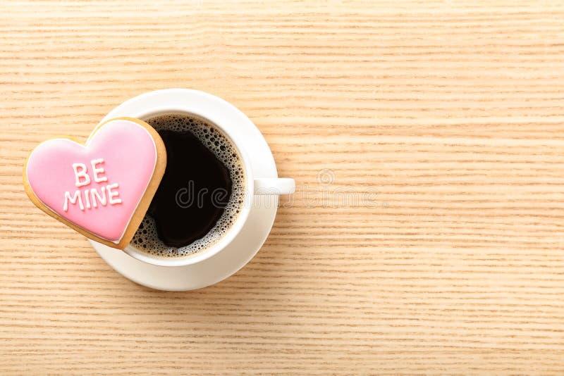 Geformtes Plätzchen des Herzens mit schriftlicher Phrase ist Bergwerk und Tasse Kaffee auf hölzernem Hintergrund, Draufsicht lizenzfreie stockfotos
