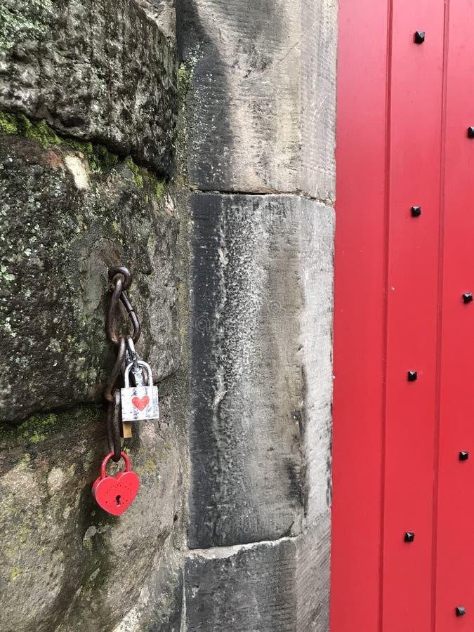 Geformtes Vorhängeschloß des roten Herzens und rote Tür lizenzfreies stockbild