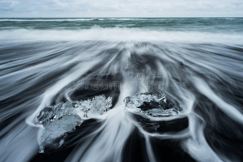 Gefrieren Sie auf Strand mit schwarzem vulkanischem Sand nahe Jokulsarlon-Gletscher L lizenzfreie stockbilder
