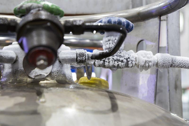 gefrieren Sie am Ventil und am Rohr des Stickstoffbehälters lizenzfreie stockfotografie