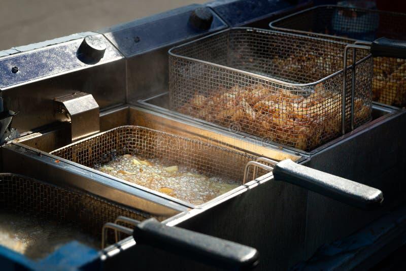 Gefrituurde aardappels Frieten in kokende olie in een braadpan worden gebraden die stock afbeelding