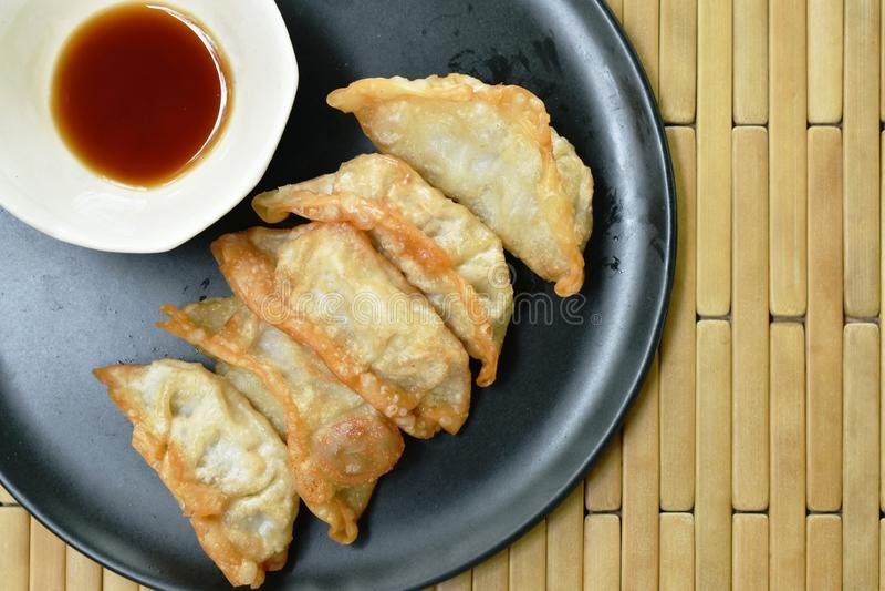 Gefrituurde Gyoza of de Japanse bol vulde de fijngehakte saus van varkensvlees onderdompelende shoyu op plaat royalty-vrije stock foto's