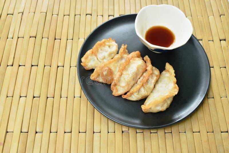 Gefrituurde Gyoza of de Japanse bol vulde de fijngehakte saus van varkensvlees onderdompelende shoyu op plaat royalty-vrije stock afbeelding