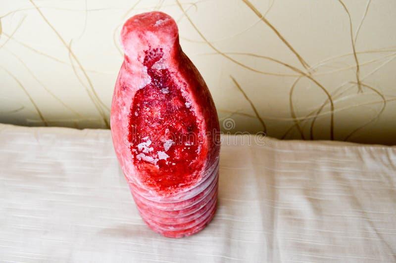 Gefroren, geschmackvoll, briet Rot Erdbeeren im Eis Gefrorene helle Beeren in Form einer Flasche in einem Schnitt lizenzfreie stockfotos