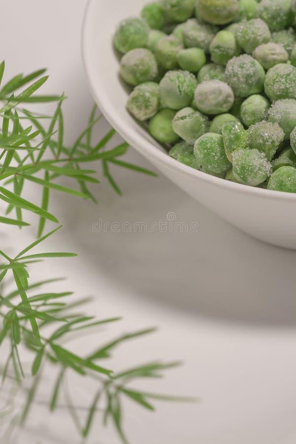 Gefrorene Erbsen in der weißen Schüssel mit grünen Kräutern stockbilder