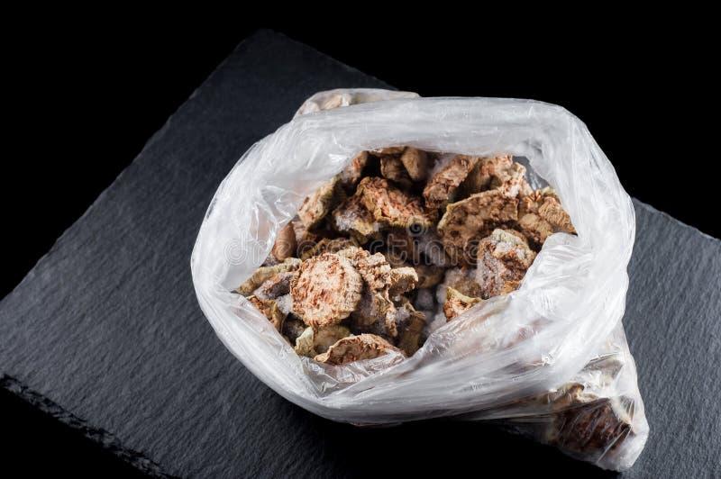 Gefrorene getrocknete Zucchini in einer Plastiktasche auf einem Steinstand auf einem schwarzen Hintergrund, Isolat lizenzfreie stockbilder
