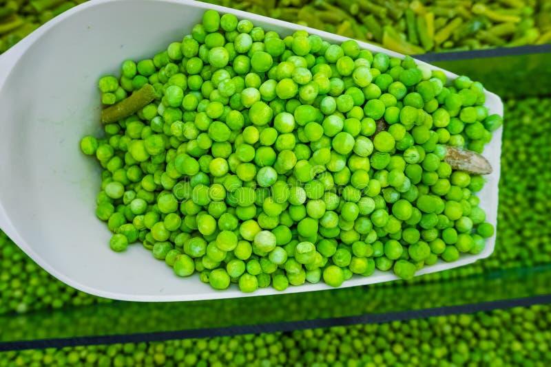Gefrorene grüne Erbsen auf einer Spachtel lizenzfreie stockbilder