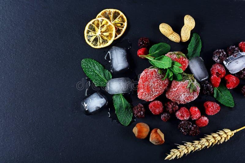 Gefrorene Himbeere, Brombeere, Erdbeertadellose Blätter, Stücke Eis auf einem schwarzen Schiefer verschalen, Scheiben der Zitrone lizenzfreie stockfotos