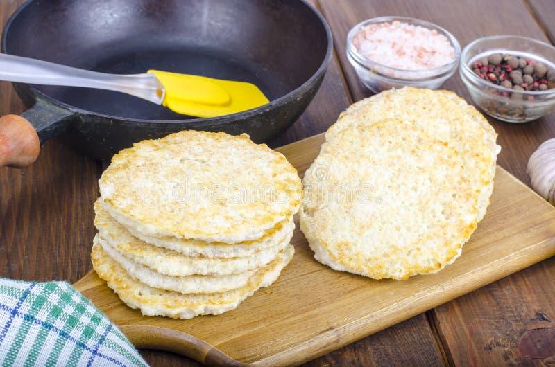 Gefrorene Pfannkuchen der rohen Kartoffel auf Schneidebrett für das Kochen lizenzfreies stockbild