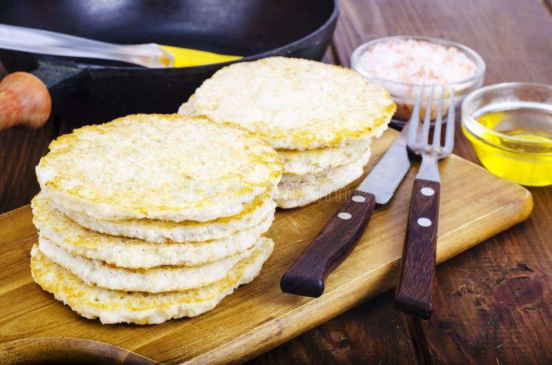 Gefrorene Pfannkuchen der rohen Kartoffel auf Schneidebrett für das Kochen lizenzfreie stockbilder