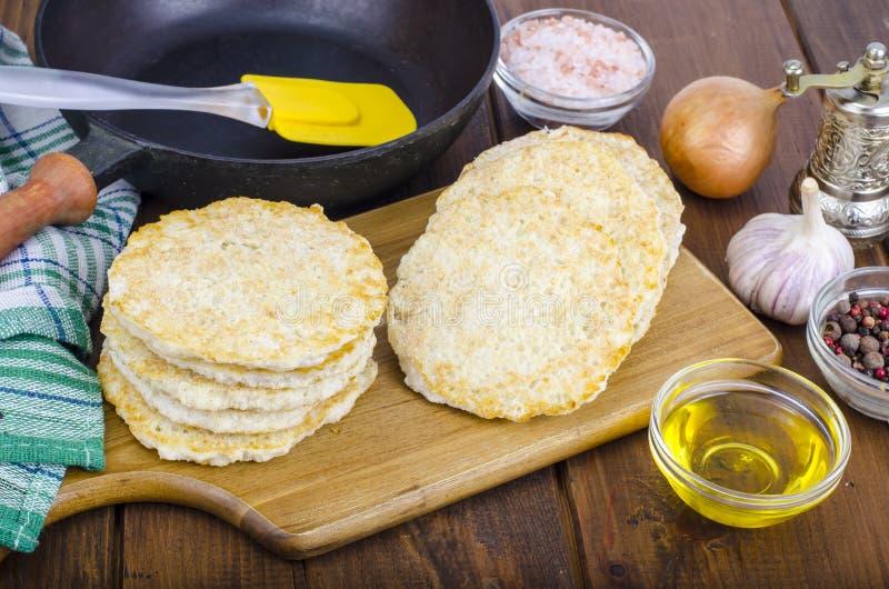 Gefrorene Pfannkuchen der rohen Kartoffel auf Schneidebrett für das Kochen stockfotos