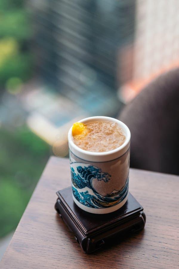 Gefrorene Pflaume Wein Umeshu-, dascocktail im keramischen Glas diente, malte japanische blaue Welle mit Unschärfehintergrund lizenzfreies stockfoto