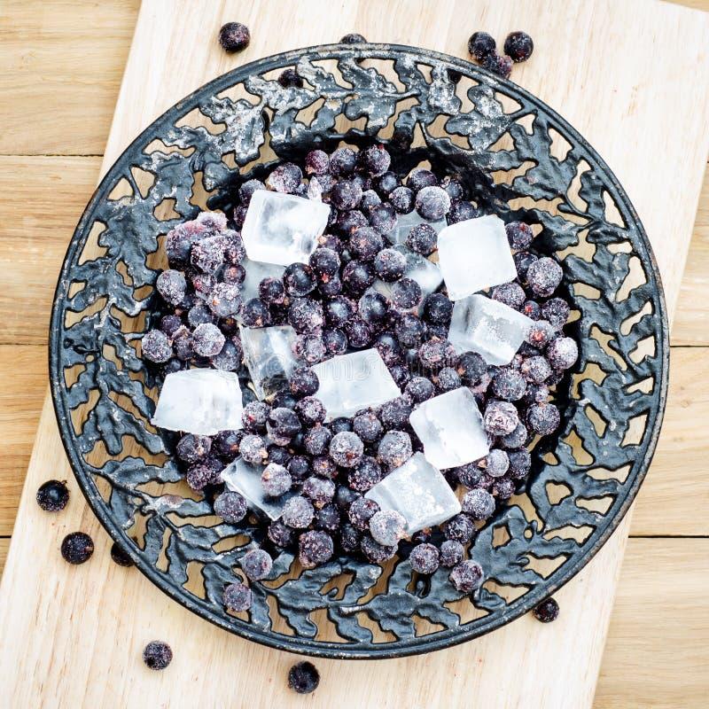 Gefrorene Schwarze Johannisbeere mit Stücken Eis auf einer Weinleseplatte stockfoto