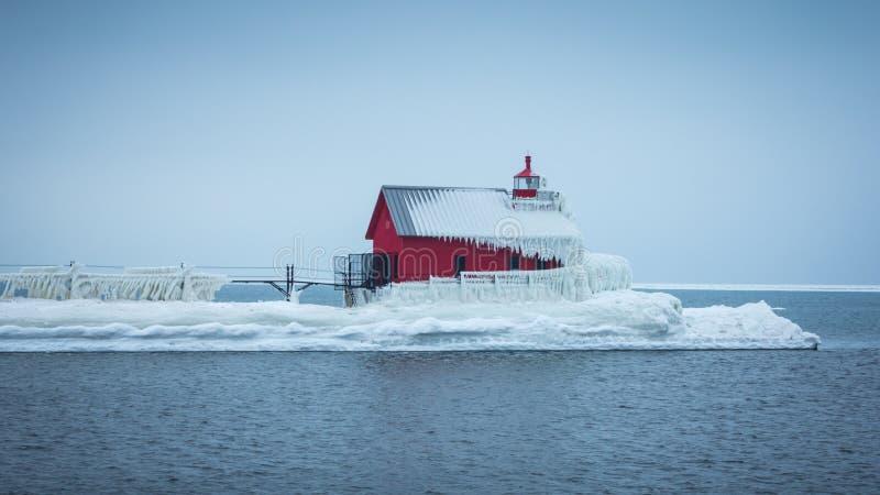 Gefrorener großartiger Hafen-Leuchtturm, der heraus in das Wasser hervorsteht stockfoto