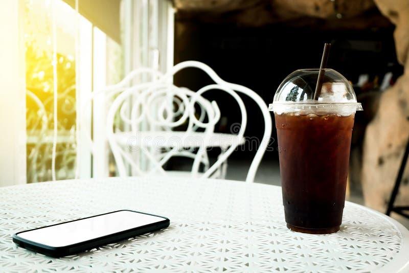 Gefrorener Kaffee americano oder schwarzer Kaffee und Smartphone auf Tabelle stockbild