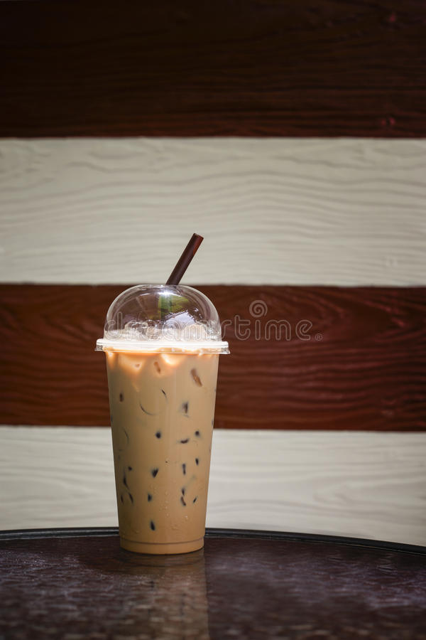 Gefrorener Kaffee in der Mitnehmerschale auf Marmortabelle mit dem unscharfen Ton zwei hölzern im Hintergrund, selektiver Fokus,  stockbilder