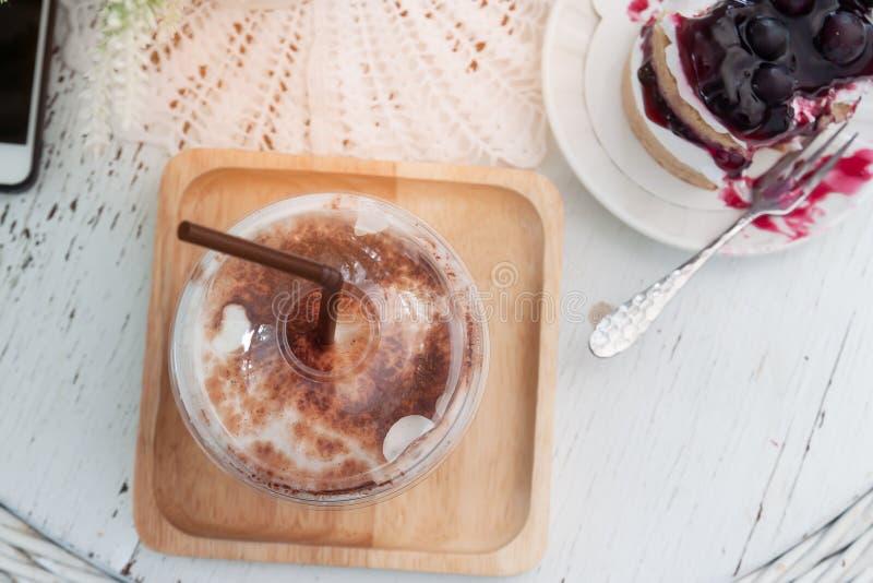 Gefrorener Kaffee und köstliche Blaubeeren backen auf Weinlesearttabelle zusammen Beschneidungspfad eingeschlossen lizenzfreies stockbild